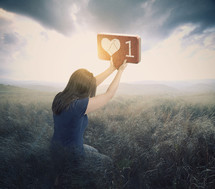 a woman kneeling holding up a one heart sign