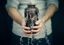 Two hands holding a broken vessel with water pouring out.