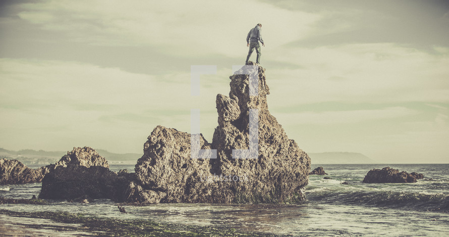 A man standing on a rock formation in the ocean.