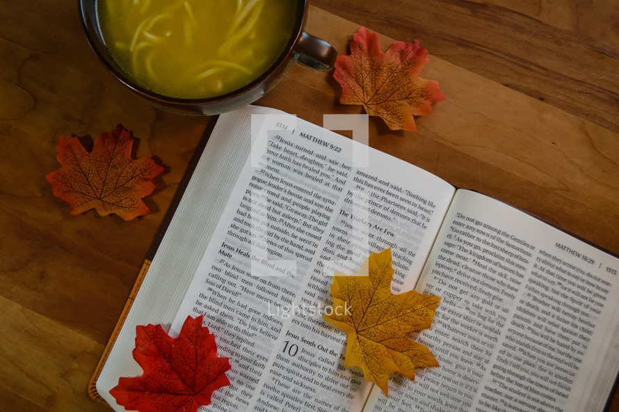 fall leaves on the pages of a Bible and chicken noodle soup