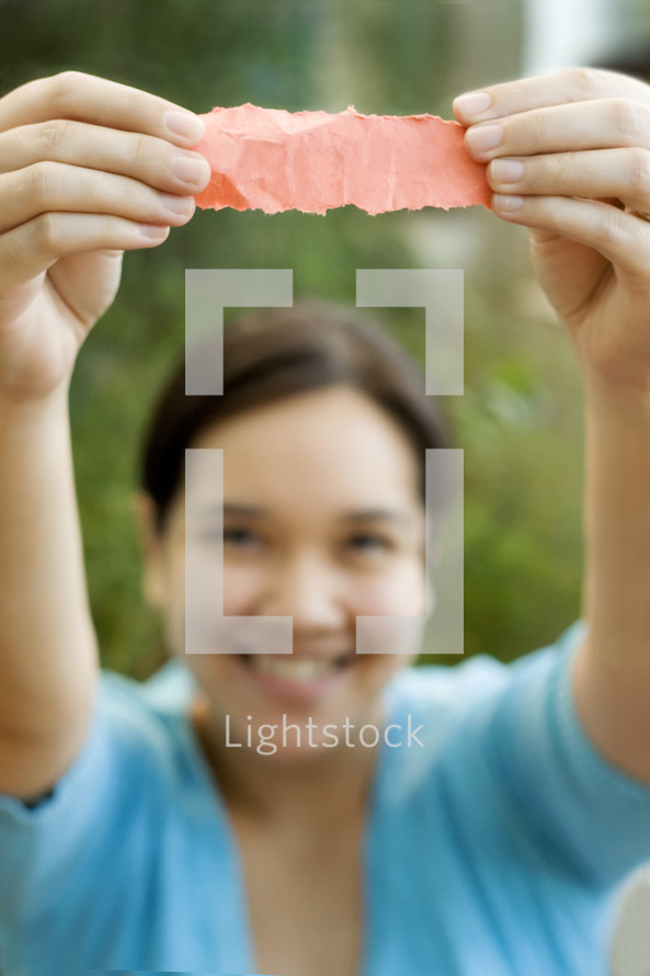 A woman holding up a scrap piece of paper