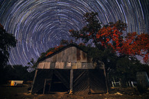 swirling stars in a night sky behind an old shed