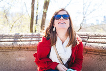 young woman wearing sunglasses looking up
