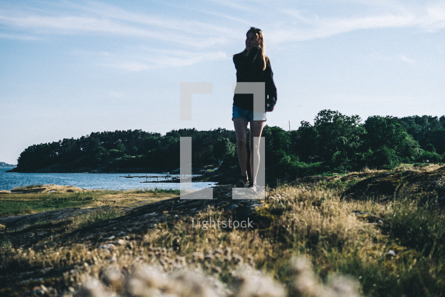 a woman standing on a shore in Sweden