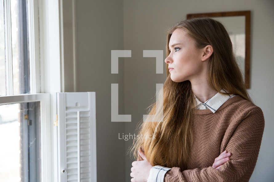 young woman standing at a window