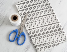 yards of patterned fabric and scissors