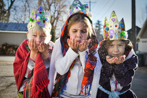 children dressed as the three kings blowing glitter