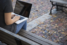 young woman sitting on a bench with a laptop on her lap