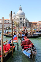 Gondolas await passengers in the Grand Canal. In the background the church of Santa Maria della Salute.