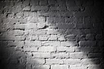Beam of light on a white, brick wall.