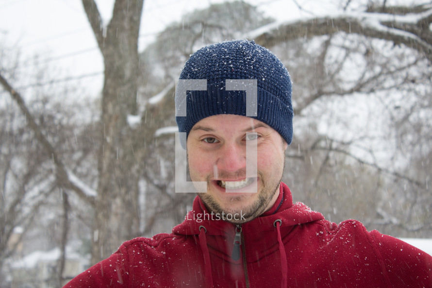 a smiling man standing outdoors in falling snow