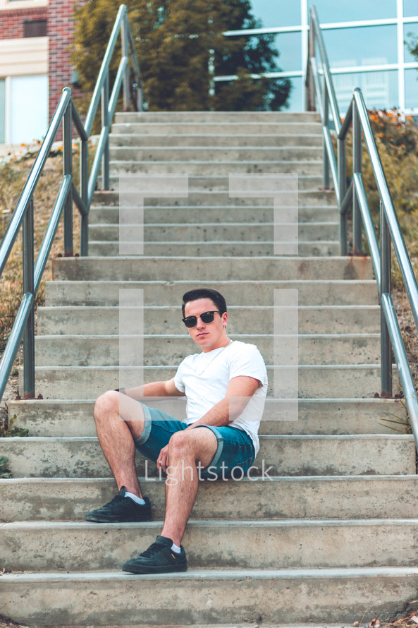 a young man sitting on concrete steps