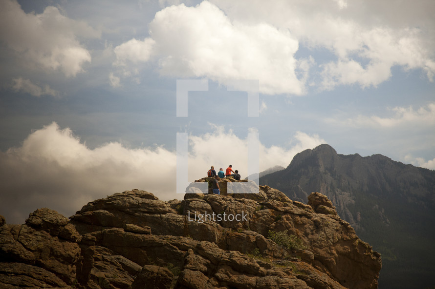 people sitting on the edge of a large rock