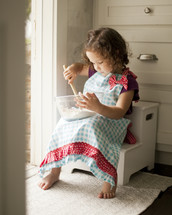 Little girl in apron baking in kitchen