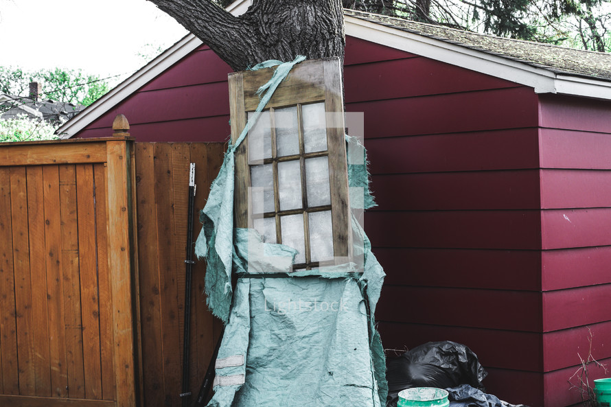 wrapped up door leaning against a shed