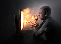 A man is hopelessly chained to a burning computer screen