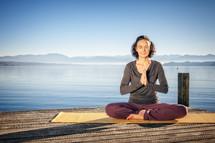 a woman meditating on a dock