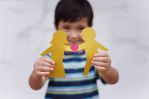 Asian child holding paper dolls