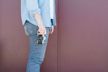 man holding a camera at his side