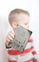 toddler boy holding an old photo