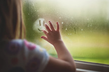 a child drawing a smiley face on a steamed up window