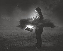 A woman holds a bright glowing Bible that shines through a dark cloud around her