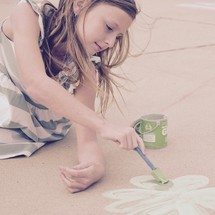 a little girl painting a green clover with sidewalk chalk paint for St Patrick's Day
