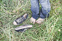 Young girl barefoot in the tall grass with sneakers.