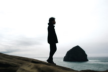 silhouette of a man standing on a rocky beach