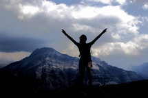 silhouette of a woman with raised arms on a mountain