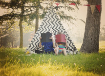 children reading outdoors in front of a teepee