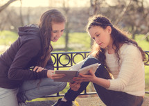 teen girls reading a journal together outdoors