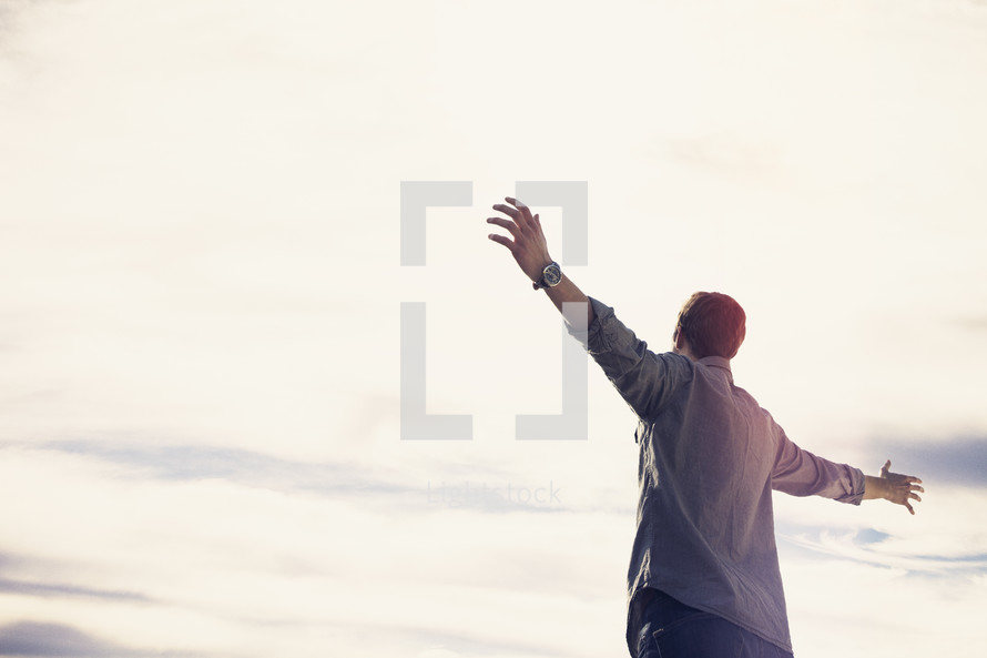 a man standing outdoors with outstretched arms