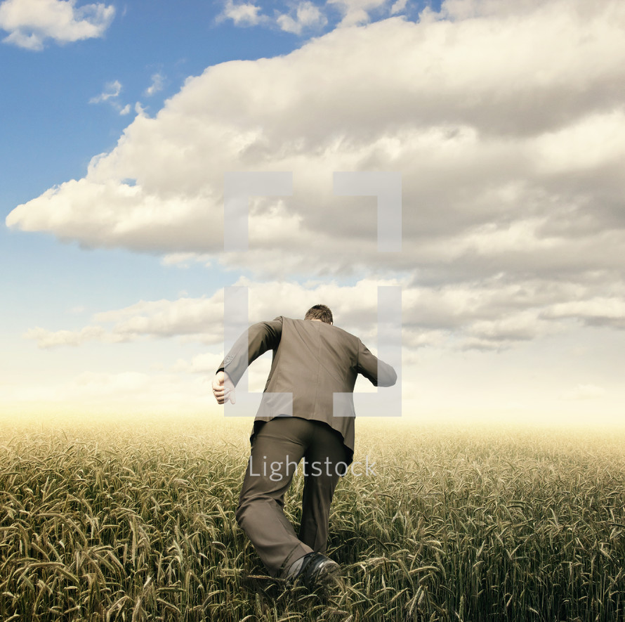 a man in a suit running through a field of wheat