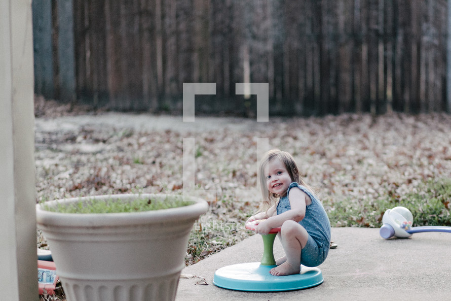 a toddler girl playing on a spinner toy