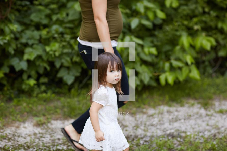 a little girl walking holding mom's hand