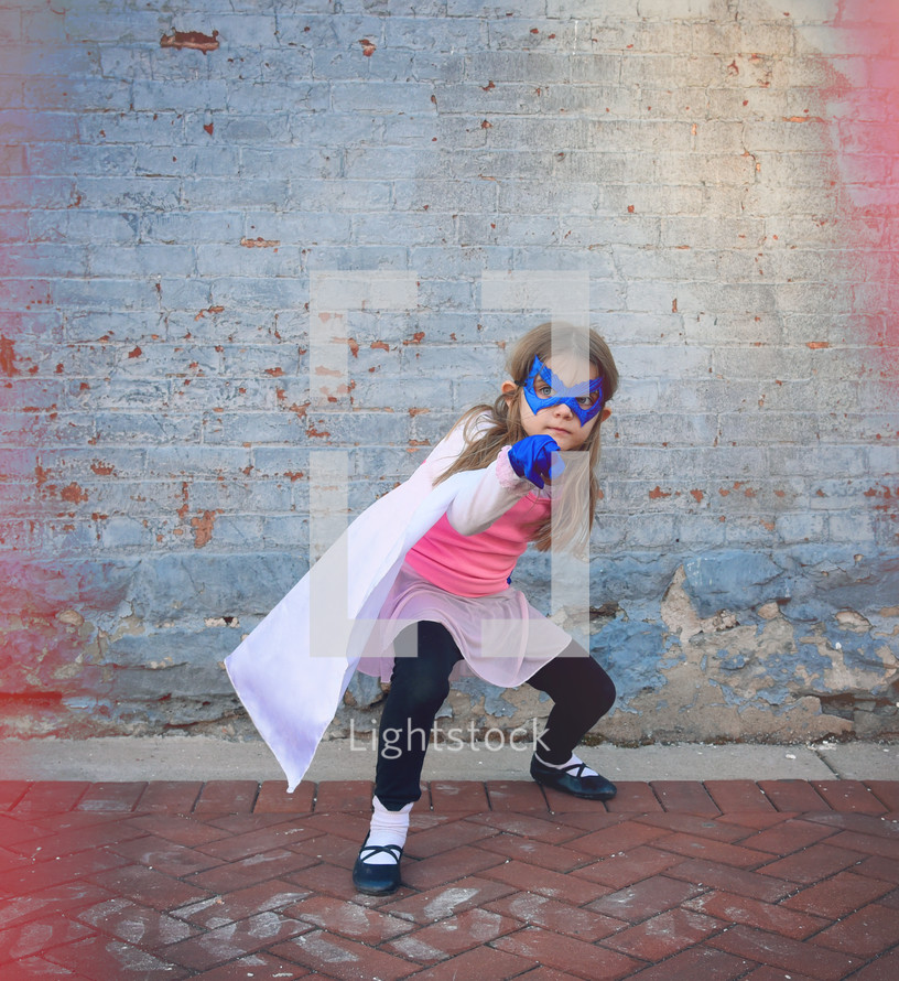 a little girl dressed up like a super hero
