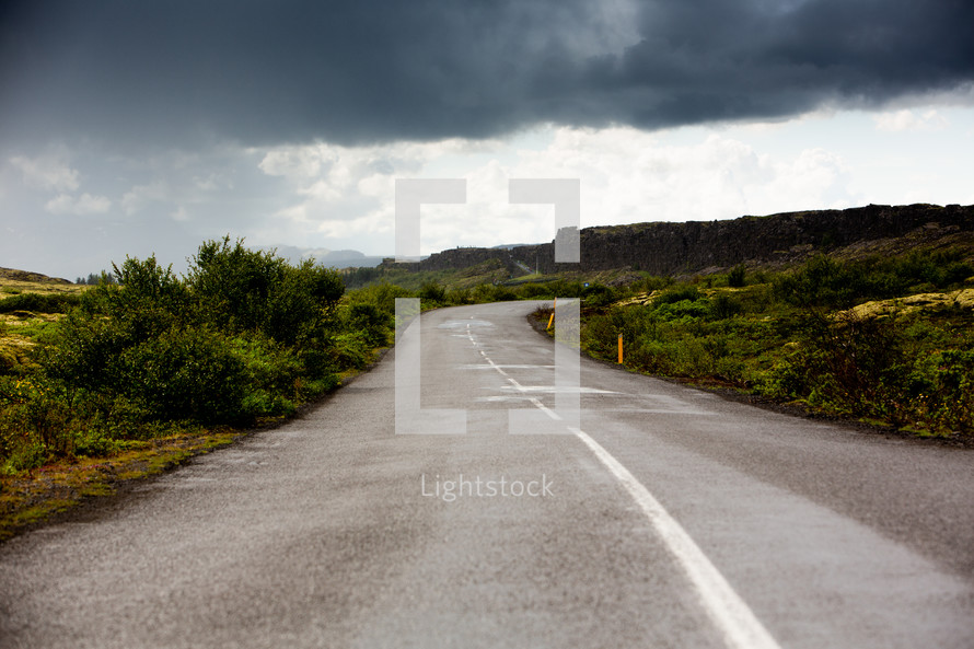 cloudy skies over a curvy road