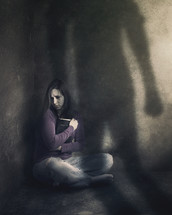 abused woman hiding in a corner holding a Bible