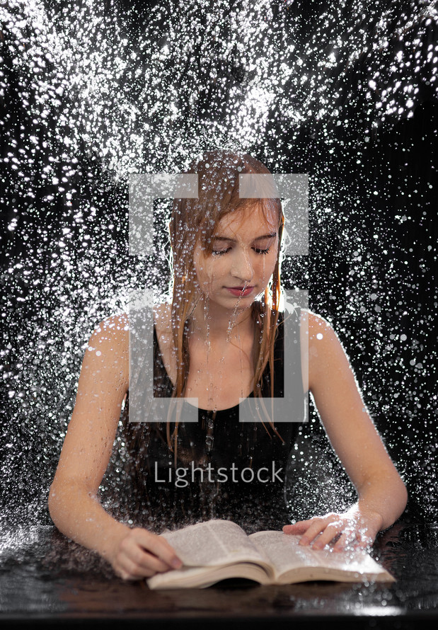 water raining down on a woman reading a Bible