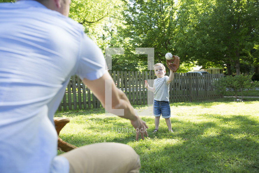 father and son throwing a baseball  together.