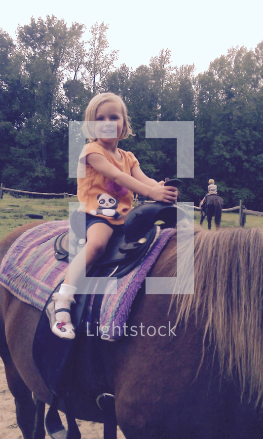 a little girl riding a pony