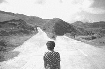 A woman standing in the middle of a road that divides into two directions.