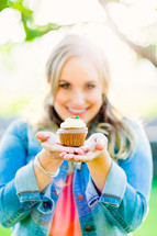 woman holding a cupcake , generosity, gift, offering