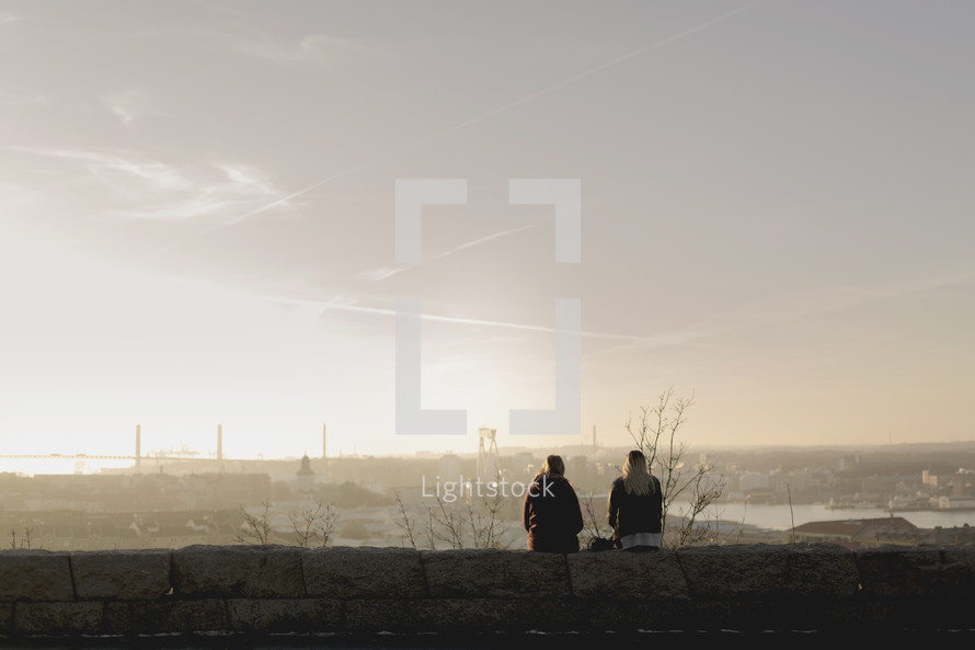 women standing on a rooftop at sunrise