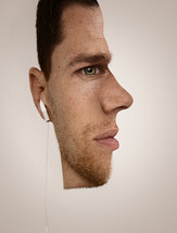 Optical illusion of half a man's face with earbuds.