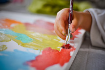 A child paints with colorful paints on a canvas.
