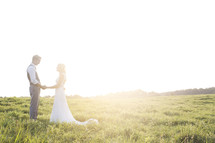 bride and groom holding hands outdoors under intense sunlight