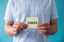 a man holding a piece of paper with the word sinner