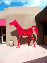 A sculpture of a red horse sits outside of an Arizona art gallery on a sunny day in the summertime.